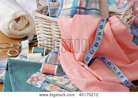 Still life image of sewing basket with pretty pastel fabrics and supplies for home decor or quilting project.  Roll of cotton batting and pinking shears in background.  Closeup with shallow dof.