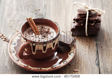 Cup of hot chocolate cocoa with cinnamon sticks on vintage wooden background, selective focus