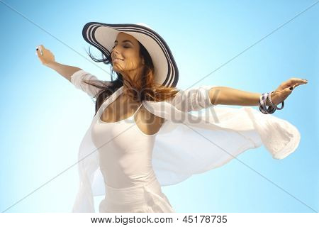 Attractive young woman pretending to fly, enjoying sun and wind eyes closed. poster