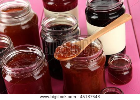 Tasty jam in banks on table close-up