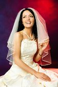 studio portrait of a beautiful happy laughing bride against red background poster
