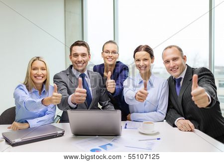 business, success, technology and office concept - smiling business team with laptop computer, papers and coffee showing thumbs up in office