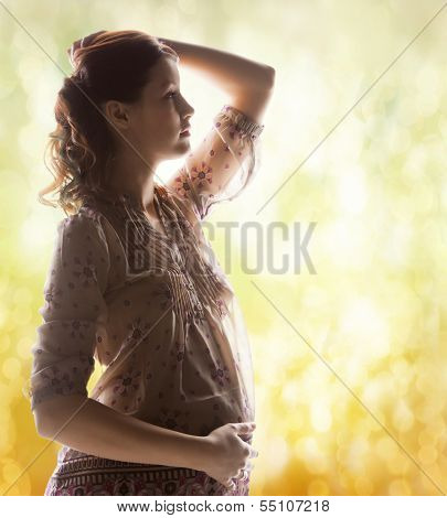 family, motherhood and pregnancy concept - silhouette backlight picture of pregnant beautiful woman touching her belly