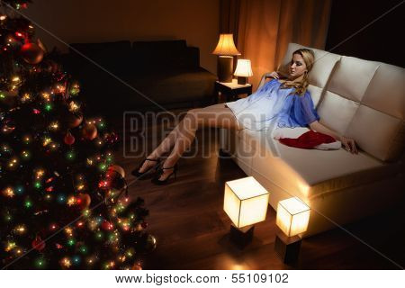 Young woman with Santa's hats  sitting on sofa remain all alone