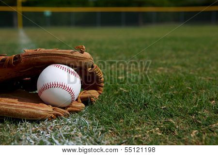 New Baseball in a Glove in the Outfield with room for copy