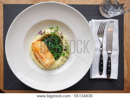 Fried fish fillet with potato mash on restaurant table