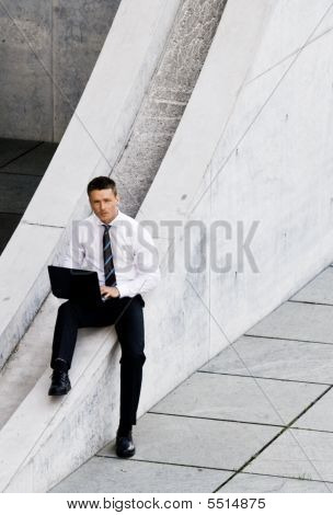 Corporate Man With Laptop Sitting Outside