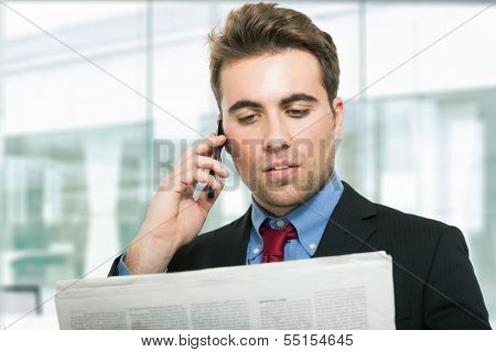 Man talking on the phone while reading the newspaper