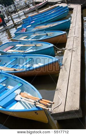 Blue Rowing Boats In Line By A Jetty