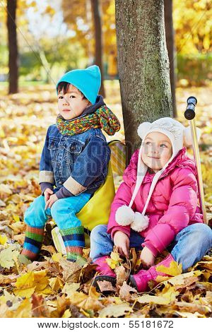 Little children sit leaning at tree trunk in autumn park, boy sits on rucksack, girl sits on push-scooter