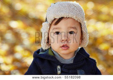 Closeup portrait of little boy in jacket and fur cap