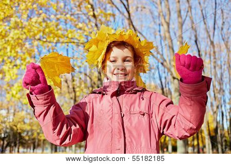 Half-length portrait of little girl in red jacket with crown made of maple yellow fallen leaves on her head in autumn park