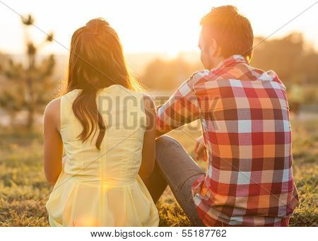 Back View Of Young Happy Couple Sitting On River. Honeymoon Concept