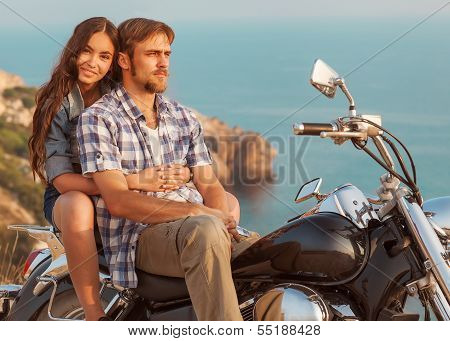 fashion couple sitting on a motorcycle at sunset