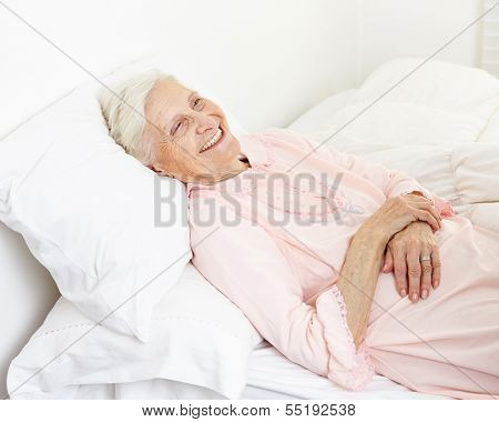 Beddridden senior citizen woman in a nursing home smiling