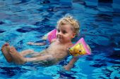 Little girl in inflatable oversleeves floats in swimming pool poster