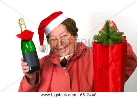 Mrs Santa Claus Santa woman dressing up in red Christmas costume is holding red sack with giftsbottlechampagneglasses spectacles; poster