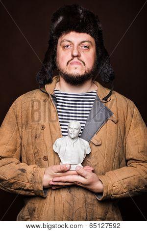 Serious russian man holding Lenin sculpture