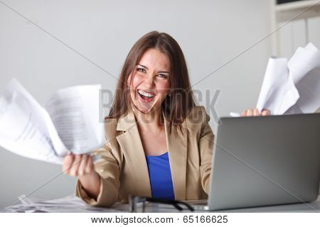 angry woman in office working with documents, laptop