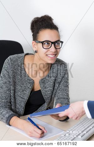 Woman Hands Over A Document To Another Woman