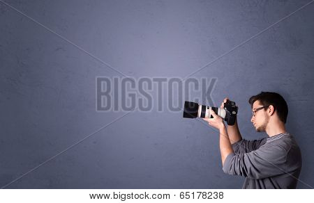 Young photographer boy shooting images with copyspace area