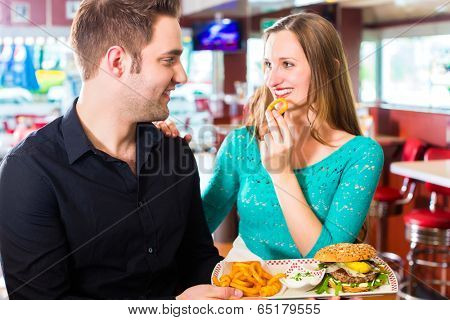 Friends or couple eating fast food with burger and fries in American fast food diner