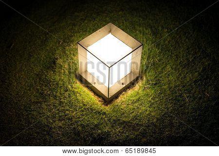 Lighting Cube Lantern On Grass At Night.