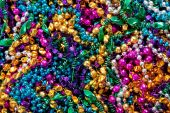 A background of colorful mardi gras beads including gold blue green pink and purple poster
