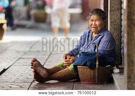 BANGKOK, THAILAND, DECEMBER 16, 2012 : Thai woman beggar sitting on the sidewalk in the Chinatown district in Bangkok, Thailand.