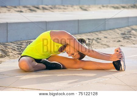 Young, flexible woman, stretching her legs on a sunny summer evening, touching her knee with her head during the warming up on a training and jogging run