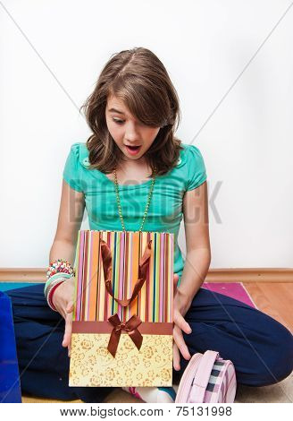 teen girl with gift bags looking inside
