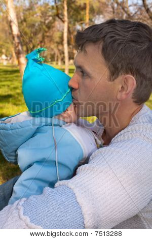The father in park on a grass sad kisses the son