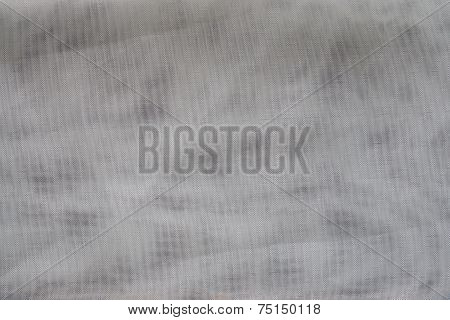 the textured background of gray color with tone spots from synthetic fabric in a grid with small cells poster