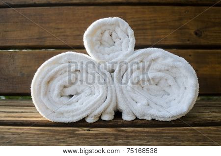 Three Rolled Towels On A Bench
