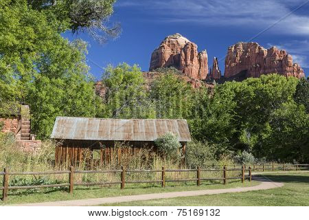 poster of Historic Crescent Moon Ranch State Park in Sedona Arizona showing abandoned ranch buildings, water mill and Cathedral Rocks in the background.
