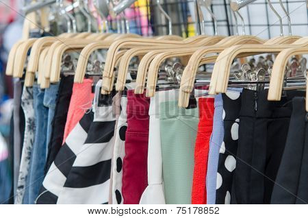 Colorful Pants hanging at a retail store on garment racks