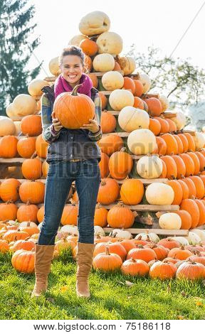 Portrait Of Happy Young Woman Holding Pumpkin In Front Of Pumpkin Piramide