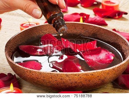 Aromatherapy. Essence oil. Spa treatment Beauty Spa treatment. Bowl of water with red rose petals