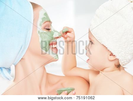 Family Beauty Treatment In  Bathroom. Mother And Daughter Baby Girl Make Mask For Face Skin