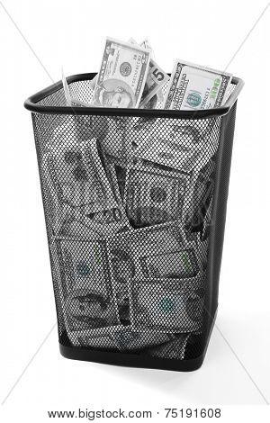 Money in dustbin on grey background