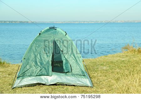 Touristic tent on dried grass near the river