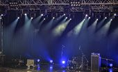 Spotlights and illumination on stage with drums amplifiers loudspeakers and other sound equipment poster