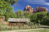 Historic Crescent Moon Ranch State Park in Sedona Arizona showing abandoned ranch buildings, water mill and Cathedral Rocks in the background. poster