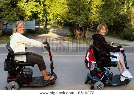 Two Happy Sisters on Mobility Scooters