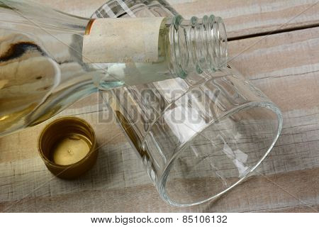Closeup of a bottle of liquor on an empty glass laying on its side. The cap is off the bottle on a rustic white wood table.