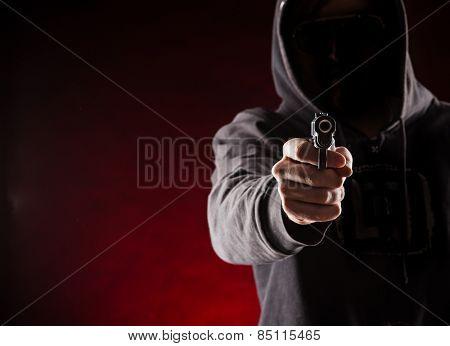 Killer with gun close-up on dark background