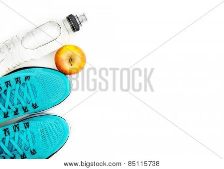 sport background: blue running shoes  and apple with objects isolated on white background