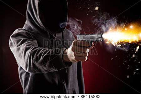 Killer with gun close-up on dark background