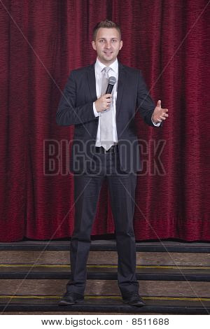 male announcer with microphone on the stage poster