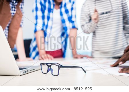 Advertising agency team in creative meeting, focus on glasses in foreground poster